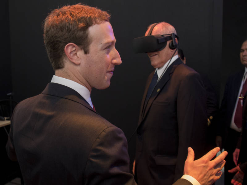 Facebook founder and CEO Mark Zuckerberg looks on a Peruvian President Pedro Pablo Kuczynski demos a virtual reality headse