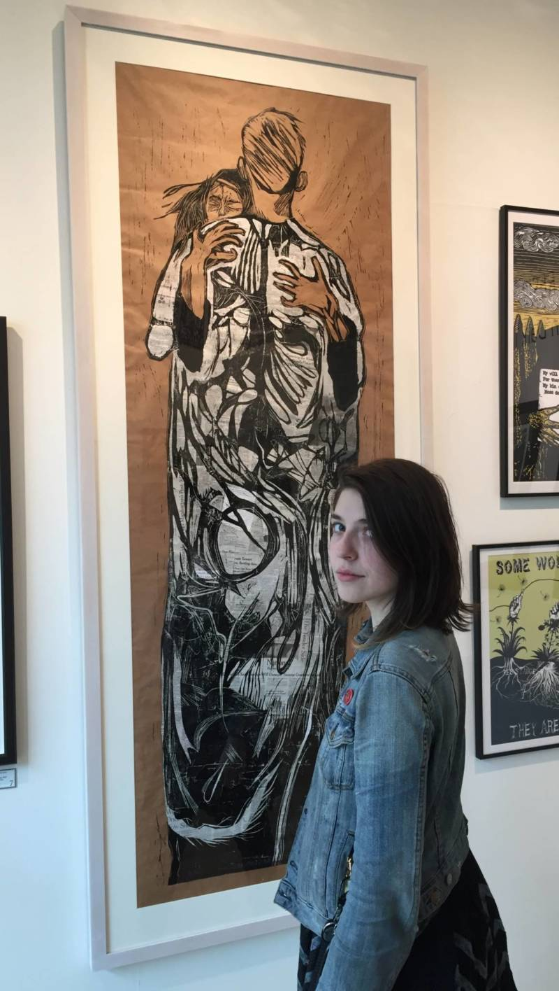 "Kate Lasker standing in front of her relief print ""Newsfeed"" part of the show 'Creation and Resistance"