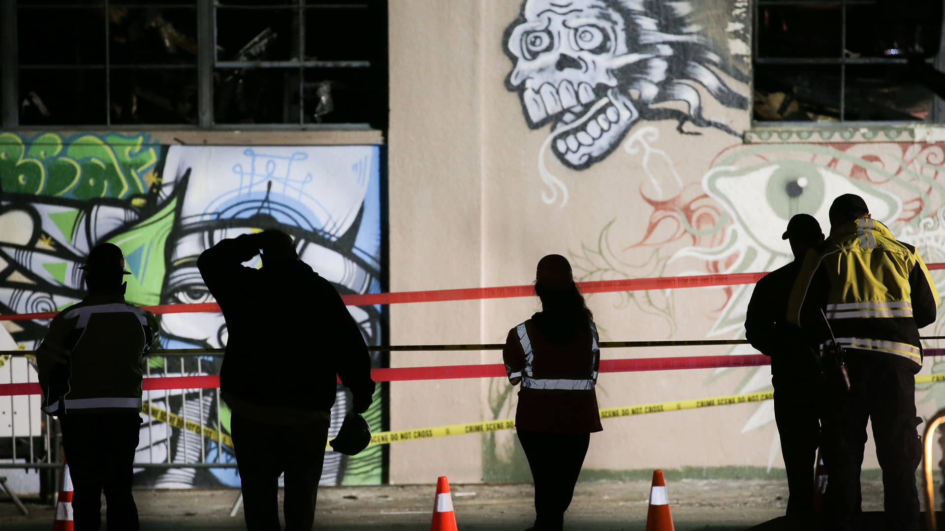 Workers and emergency responders look at a warehouse in which a fire claimed the lives of at least thirty-six people on Dec. 5, 2016 in Oakland, California.