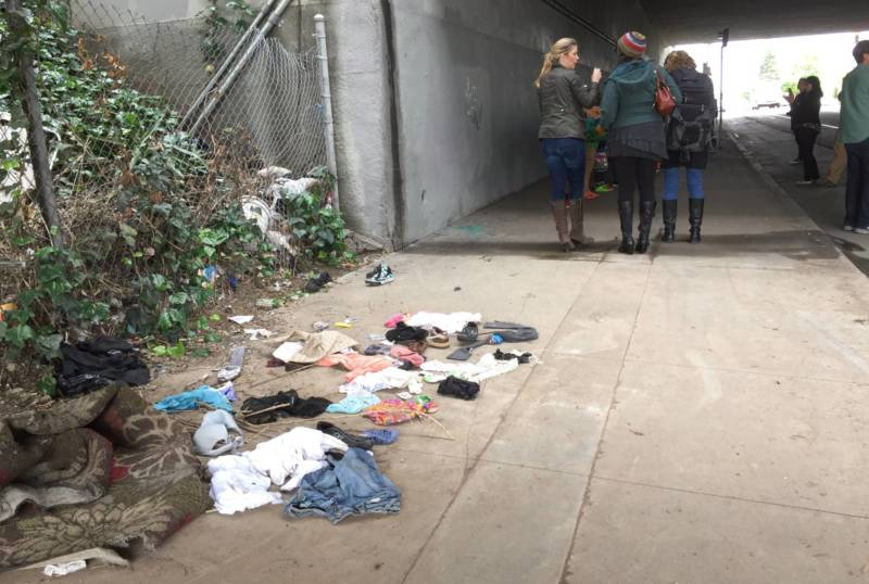 Trash and old clothes litter the sidewalk of an I-580 freeway underpass on West Street in Oakland