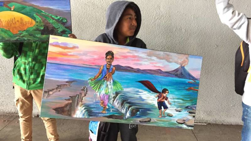 A Hoover Elementary 4th grader holds a canvas showing a section of the planned mural for the I-580 underpass wall behind him
