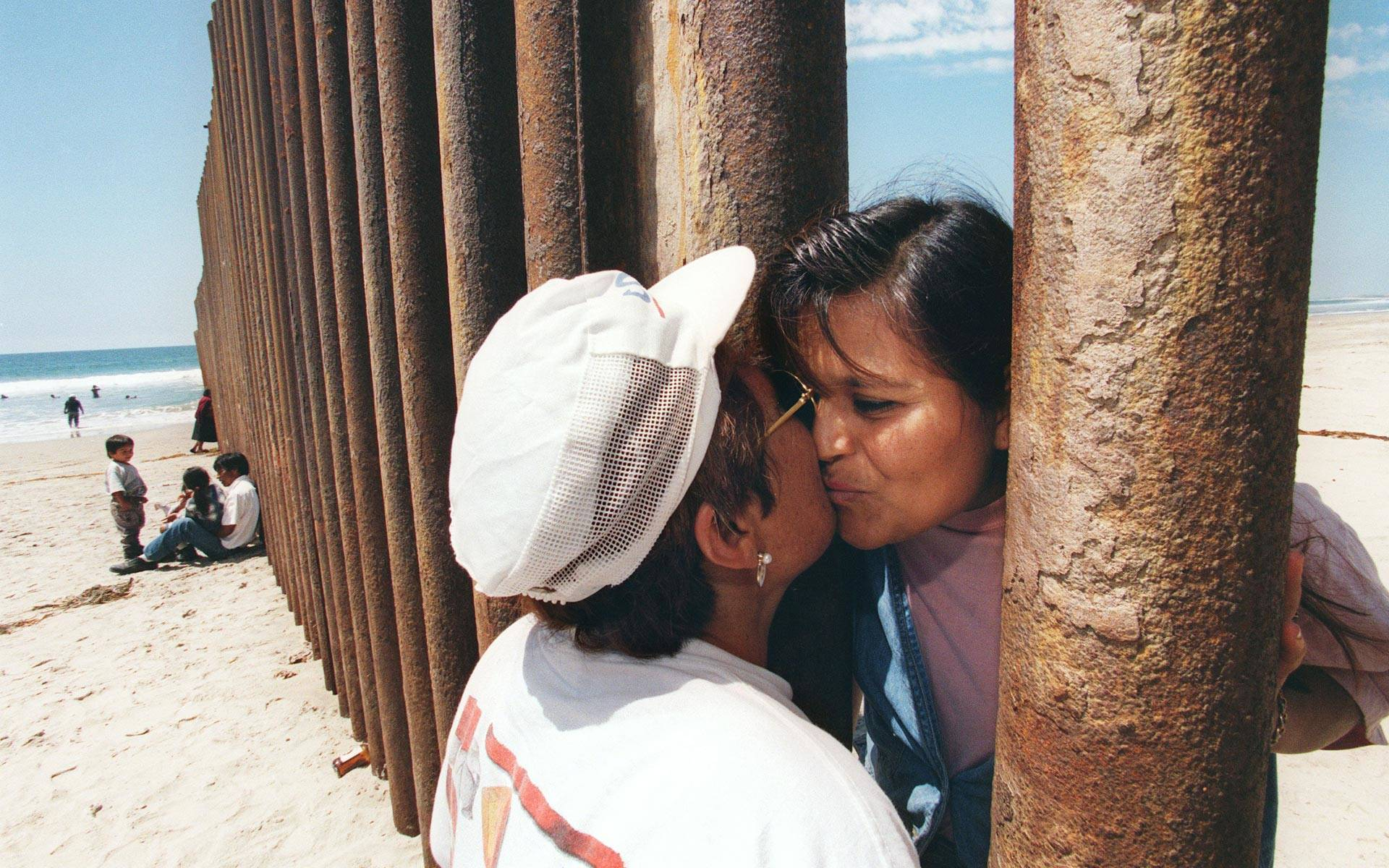 Esther Pereyra Rubalcaba (L) kisses her daughter Patricia through the wall separating the US and the Mexican territories in Tijuana, Mexico, on August 19, 1997. Photo: Hector Mata/AFP/Getty Images
