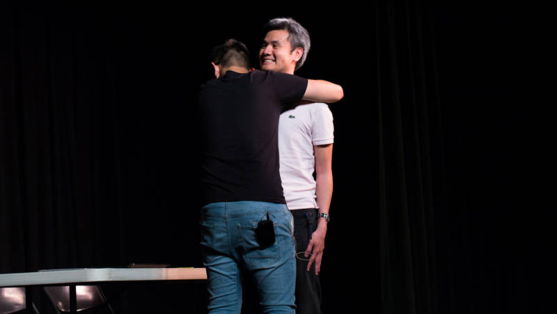 "In ""Awkward Hug,"" a son, played by Stanford student Jason Li, has to beg for a physical expression of affection from his father, played by Dr. Steven Sust."