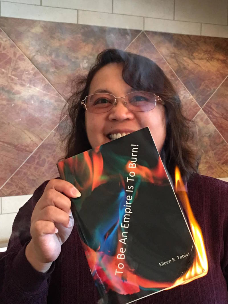 Poet Eileen Tabios with her poetry chapbook 'To Be An Empire Is To Burn!' -- which she set on fire to reflect its title.