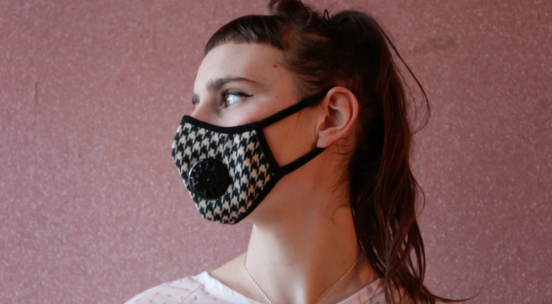 white femme from the neck up. she looks to her right and is wearing a houndstooth patterned chemical mask.