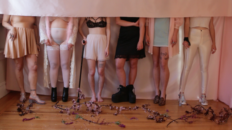 Image description: photo. six people stand facing forward, visible only from the neck down.. a pink fabric hangs and covers their faces in a horizontal line. some use canes. they stand on a wood floor covered with flower petals