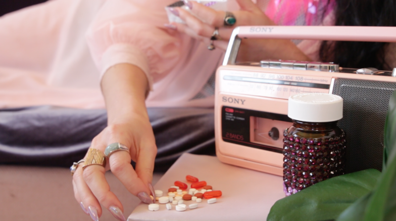 Image Description: photo. a person wearing a light pink nightgown sorts orange and white pills. she has pink opalescent nails. there is a pink radio, a bedazzled pill jar, and a green plant to the right.