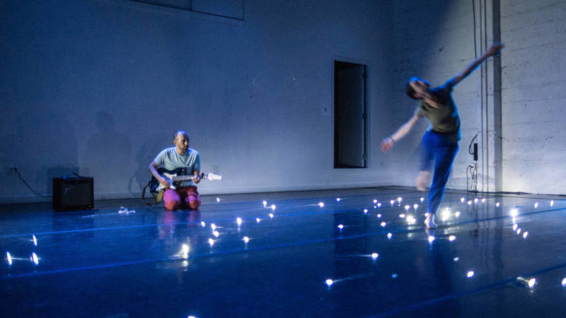 Adam Smith plays the guitar while Arletta Anderson dances through the universe in 'weather//body' at CounterPulse.