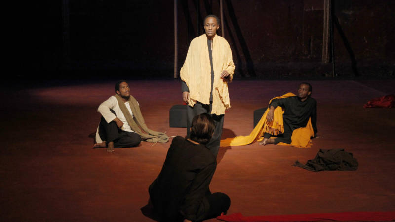 (Sitting L to R) Yudishtra (Jared McNeil), Dritarashtra (Sean O'Callaghan), Bishma (Ery Nzaramba) listen to Kunti (Carole Karemera) tell a story in 'Battlefield' directed by Peter Brook and Marie-Hélène.