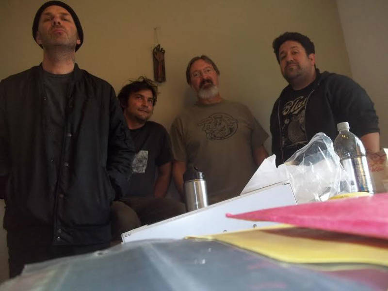 Tim Armstrong, Murray Bowles, Robert Eggplant and Corbett Redford, sorting through Bowles' 30,000-strong photo archive.