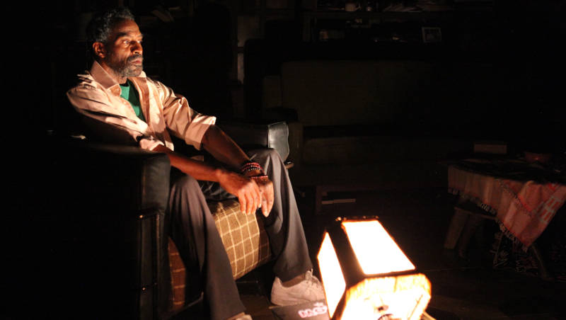 Gil Scott-Heron (Carl Lumbly) sits in the darkness in 'Grandeur' by Han One.