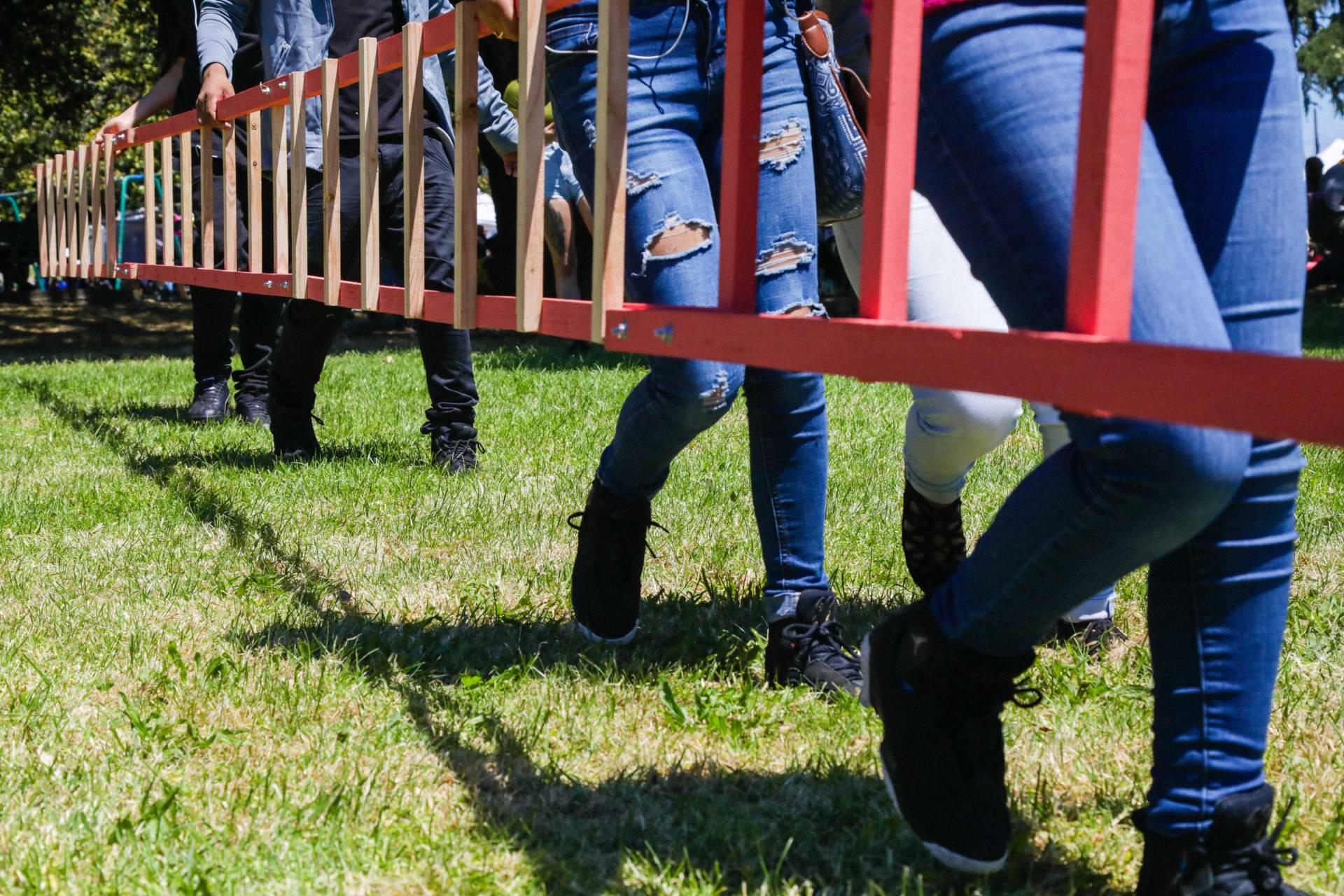 Urgent Art workshop students navigating their ladder sculpture through San Antonio Park.  Farrin Abbott