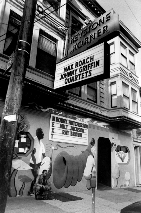 Exterior view circa 1982 of the Keystone Korner in North Beach. Saxophonist Odean Pope of the Max Roach Quartet poses in front.