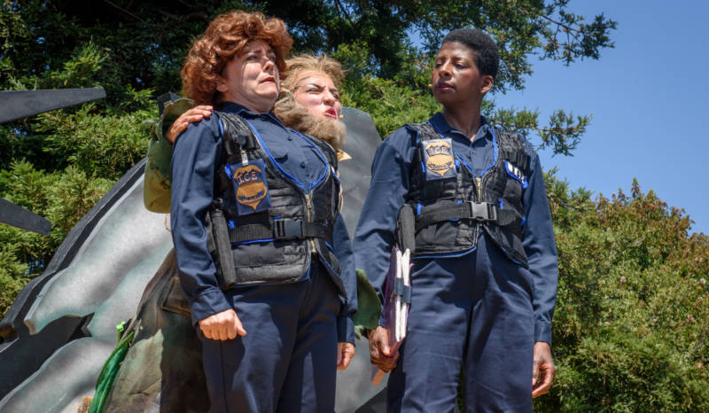 ICE Agent Cliodhna Abhabullogue (Lizzie Calogero), Leprechaun (Marilet Martinez) and L. Mary Jones (Velina Brown) discuss the meaning of immigration in 'Walls' by the San Francisco Mime Troupe.