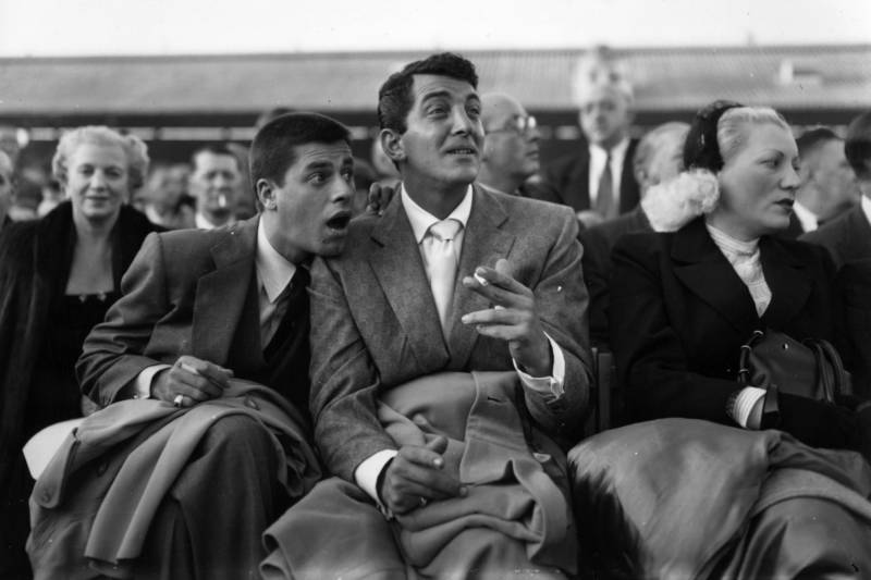 Dean Martin (center) sits with Lewis in 1953 at a boxing match.