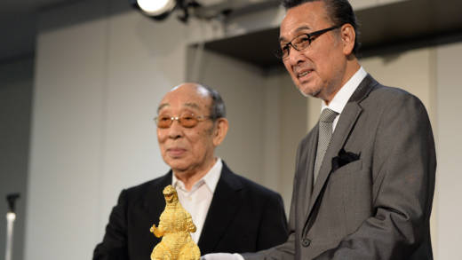 Japanese actors Akira Takarada (R) and Haruo Nakajima (L) pose beside the 24-cm-tall and 15-kilogram gold statue of Godzilla unveiled during a press preview of the Godzilla exhibition in Tokyo on July 19, 2014.