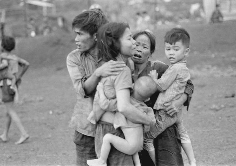Civilians huddle together after an attack by South Vietnamese forces. Dong Xoai, June 1965.