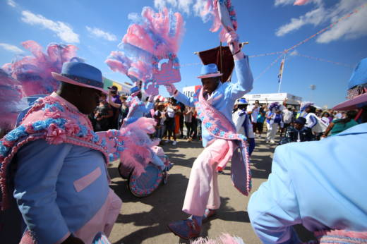 A second-line parade at the 2017 New Orleans Jazz and Heritage Festival, one of many sights underlining the event's place-based identity.