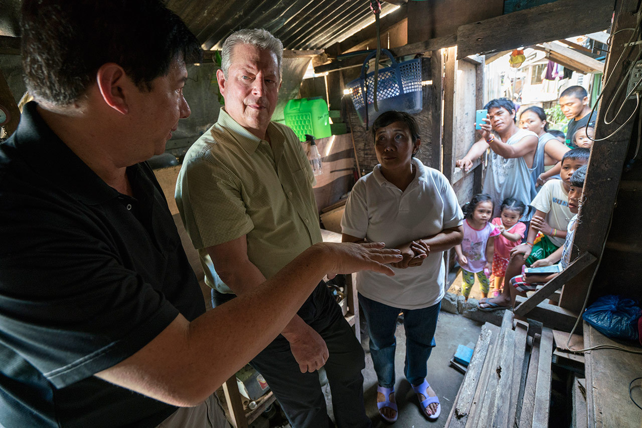 Al Gore with former Mayor of Tacloban City Alfred Romualdez and Typhoon Haiyan survivor Demi Raya, in the Raya family home; Tacloban City, Philippines, March 12, 2016.