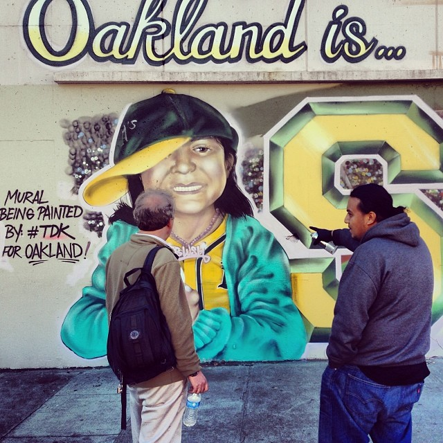 Amend shows a passerby his A's mural-in-progress in Jack London Square.