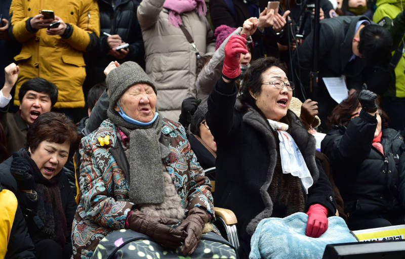 """South Korean former """"comfort women"""" Lee Yong-Soo (R) and Gil Won-Ok (C), who were forced into wartime sexual slavery for Japanese soldiers, shout slogans during an anti-Japanese rally commemorating the death of nine former sex slaves this year in front of the Japanese embassy in Seoul on December 30, 2015. South Korean """"comfort women"""" and supporters vowed to step up protests against a deal between Seoul and Tokyo on resolving a long-running row over the comfort women."""