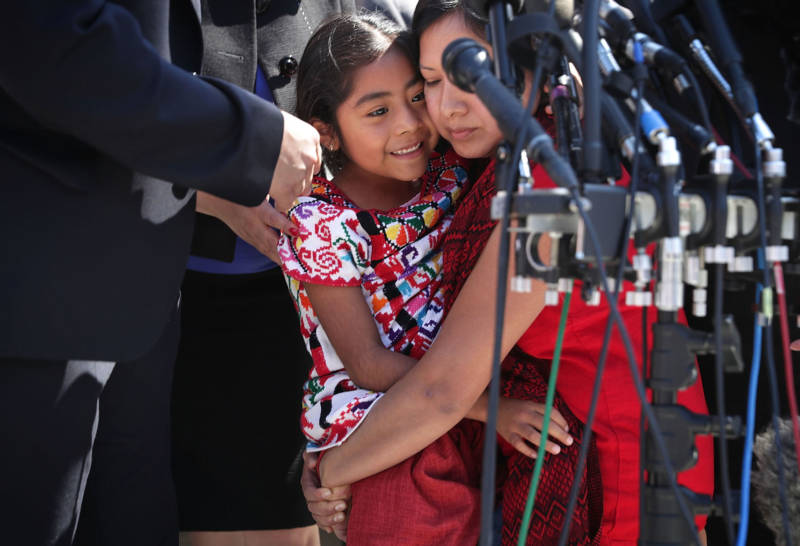 Six-year-old Sophie Cruz (L) of Los Angeles is held by her mother Zoyla Cruz (R) after she spoke to members of the media in front of the U.S. Supreme Court April 18, 2016 in Washington, D.C.
