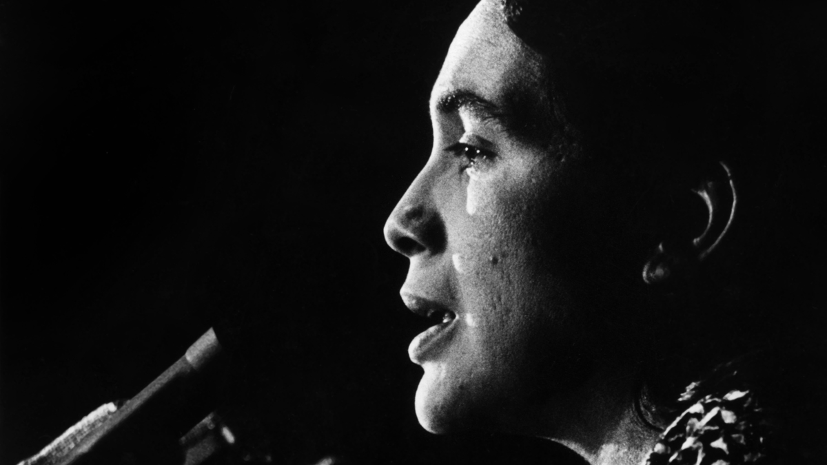 Dolores Huerta speaks at the podium, circa 1970s.