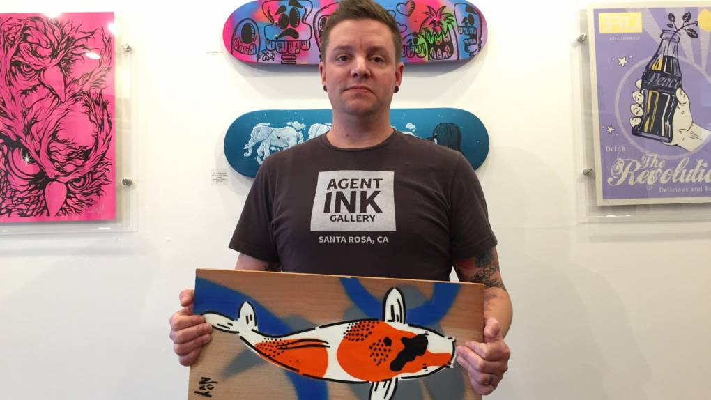 Agent Ink's Curt Barnickel holding a painting that will be auctioned at a fundraiser at the gallery Nov. 11