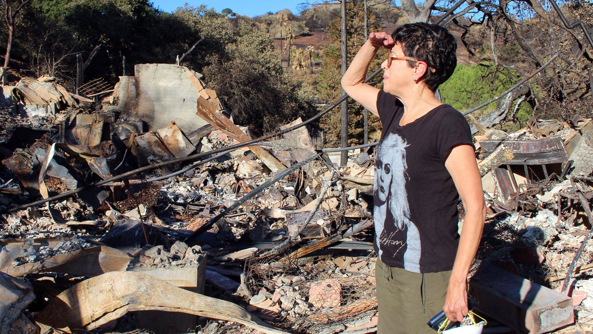Norma Quintana searches through the remains of her home near the Silverado Country Club in Napa. Quintana has started photographing items she finds in the ashes for a series called 'Forage From Fire.'