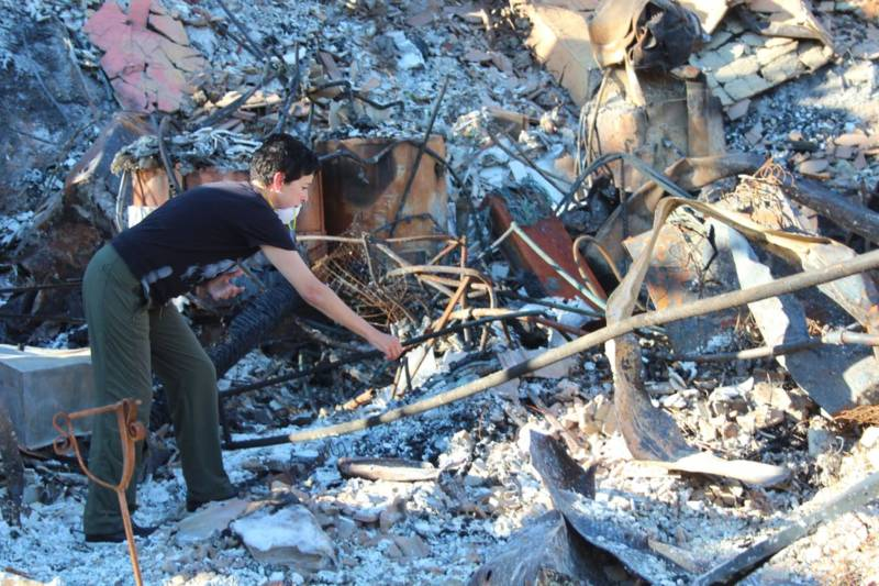 Norma Quintana searches for items in the ashes of her Napa home.