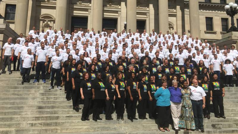 Members of The San Francisco Gay Mens Chorus and the Oakland Interfaith Gospel Choir gather on the steps of the Mississippi State Capitol to sing.