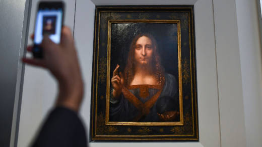 "A journalist takes a photo of Leonardo da Vinci's ""Salvator Mundi"" after it was unveiled at Christie's in New York on October 10, 2017. One of fewer than twenty painting by Leonardo da Vinci and the only one in private hands, the Salvator Mundi sold for more than $450 million on Nov. 15, 2017, at Christie's New York."