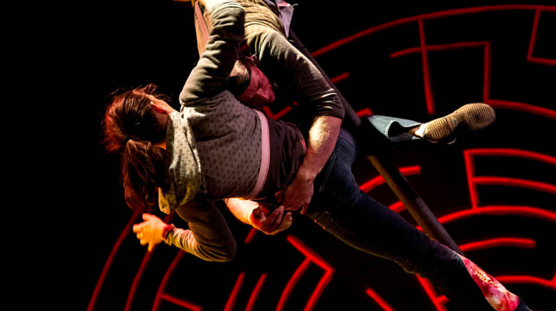 Jane Doe (Emily Rose Phillips) hangs onto Frank Conner Ponzi III (Ross Tavis) rather high up in the air in 'Circus Veritas' produced by Kinetic Arts.