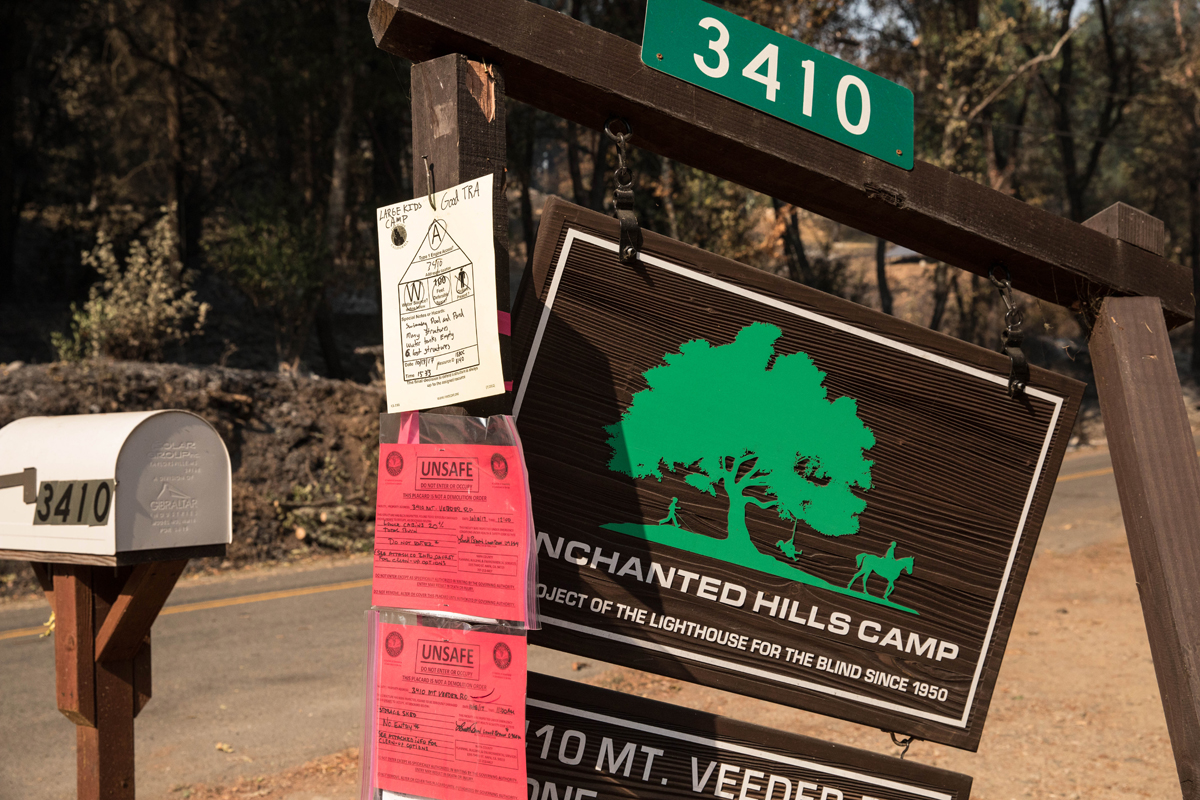 Off-kilter Enchanted Hills Camp sign, still marked 'unsafe.'