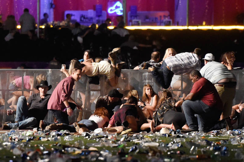 People scramble for shelter at the Route 91 Harvest country music festival in Las Vegas after a gunman opened fire, leaving 59 people dead and more than 500 injured, on Oct. 1, 2017.