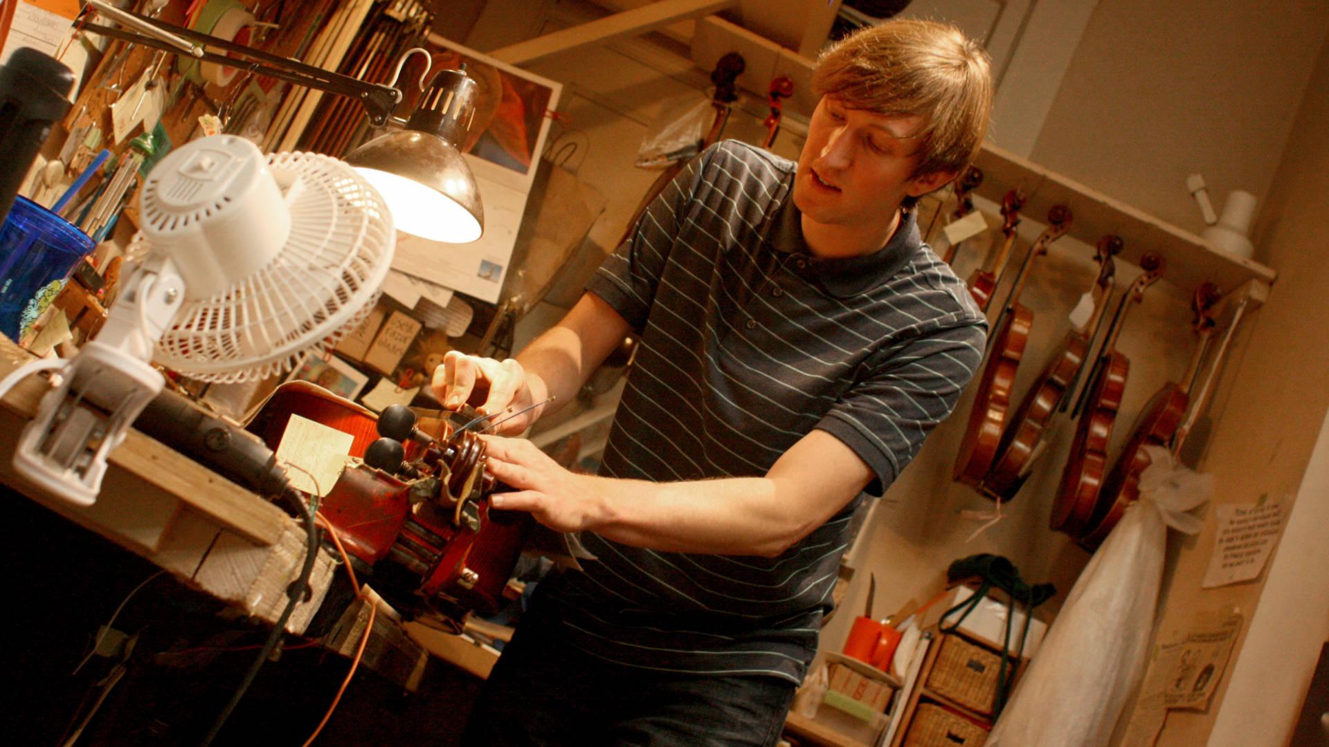 Julian Loveland works on a cello in his family's Santa Rosa shop.