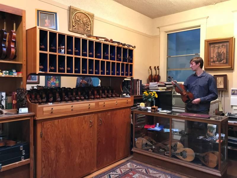 Julian Loveland behind the counter at the Loveland Violin Shop.