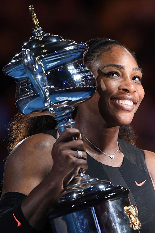 Serena Williams of the US celebrates with the championship trophy during the awards ceremony after her victory against Venus Williams of the US in the women's singles final on day 13 of the Australian Open tennis tournament in Melbourne on January 28, 2017.