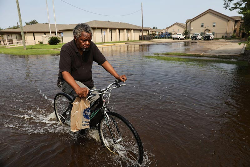 A man returns from the grocery store through high water along a street in Orange as Texas slowly moves toward recovery from the devastation of Hurricane Harvey on September 6, 2017 in Orange, Texas.
