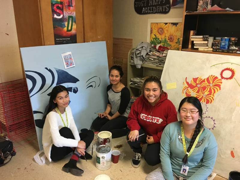 Pinole Valley High students pose in front of their work.