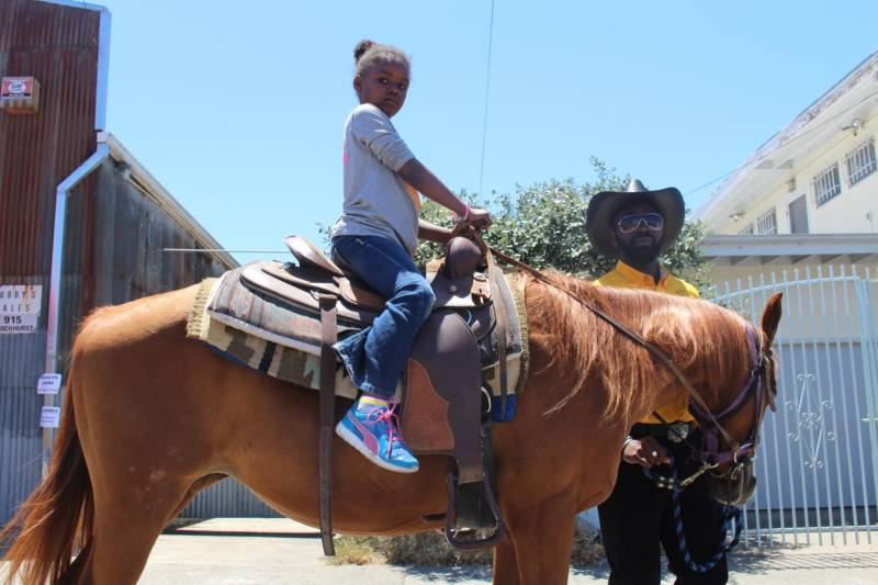 A young lady rides a horse, as a member of the Black Cowboys chaperones her, at a Juneteenth festival in East Oakland.