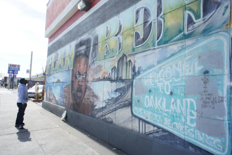 Rapper Ian Kelly takes a long look at one of the longest standing murals in Oakland, the image of slain East Oakland rapper Plan Bee.