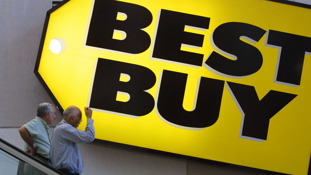 Customers pass underneath a Best Buy sign