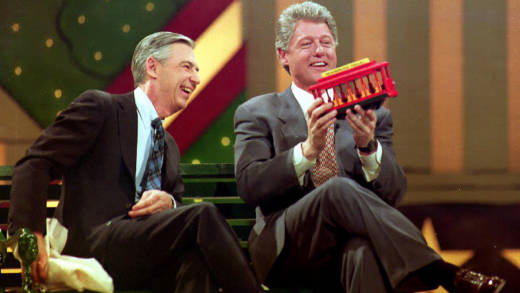 Bill Clinton (R) holds a trolley car given to him by Fred Rogers (L) during the Presidential Inaugural Celebration for Children 19 January 1993 at the Kennedy Center.