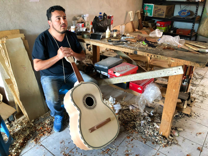 César Ivan Lemus, a third-generation Paracho artisan, shaves the neck of a <em>guitarrón</em> he's making. Lemus sells all types of instruments to mariachi schools and stores in the U.S. He says he's working as fast as he can to keep up with orders these