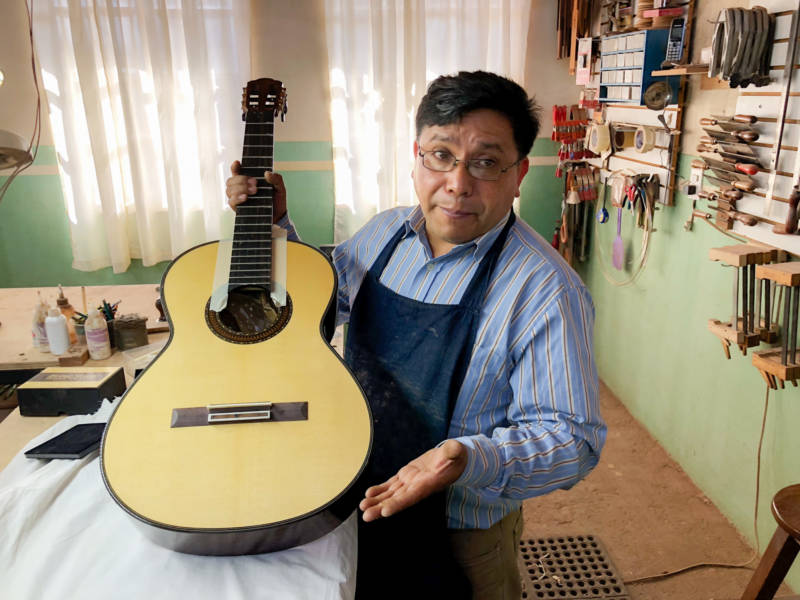 Master guitar maker Arnulfo Rubio Orozco holds up his latest project. It's taken him a month to craft this guitar with pearl accents and wood from southern Mexico
