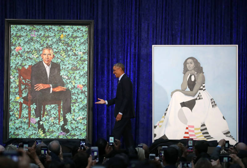 Former President Barack Obama stands with his and former first lady Michelle Obama's newly unveiled portraits during a ceremony at the Smithsonian's National Portrait Gallery in Washington, D.C.