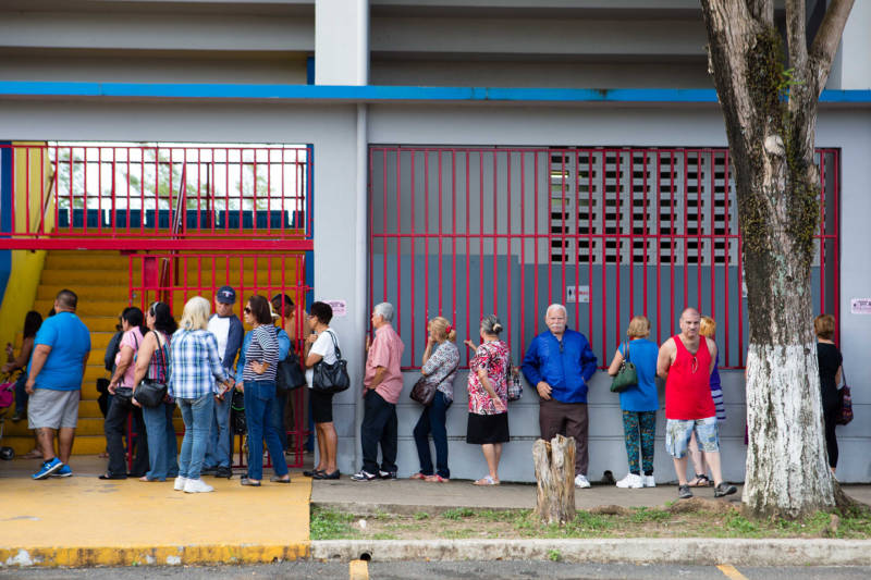 Residents of Aguada, Puerto Rico, stand in line for food aid at a FEMA distribution center on February 7, 2018. Local officials, including police, distribute supplies provided by FEMA once a week.
