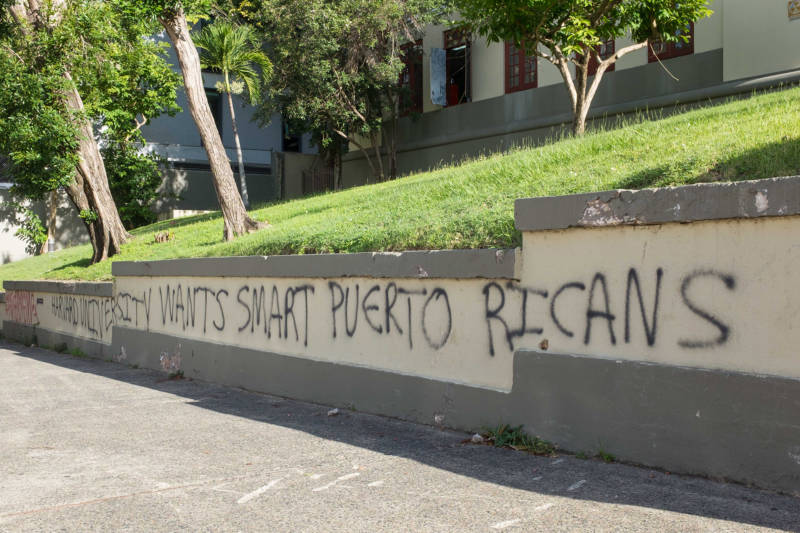 "Grafitti on the steps of a high school in San Juan reads, ""Harvard University wants smart Puerto Ricans."" Out-migration of Puerto Ricans, or ""brain drain,"" is a long-standing problem that has been accelerated in the wake of Hurricane María. Independent artists are especially vulnerable since shows and recording studios have been slow to recover."