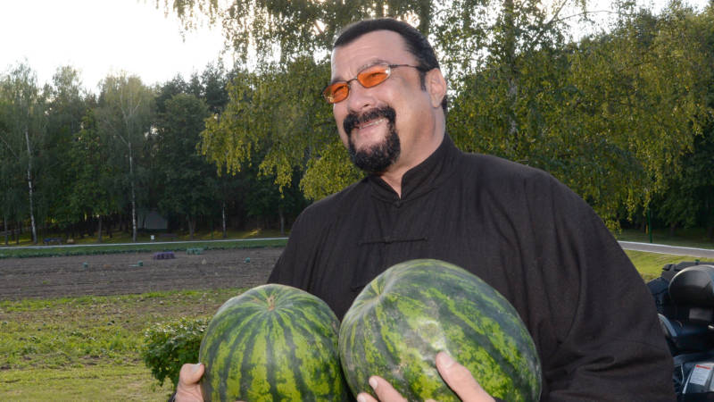 Steven Seagal holds two water melons during his meeting with the Belarus President at his residence of Drozdy, outside Minsk, on August 24, 2016.